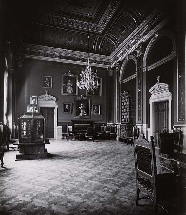 Old photo of the Chancellor's Room. A chandelier hanging from the ceiling, a showcase stand on the floor.