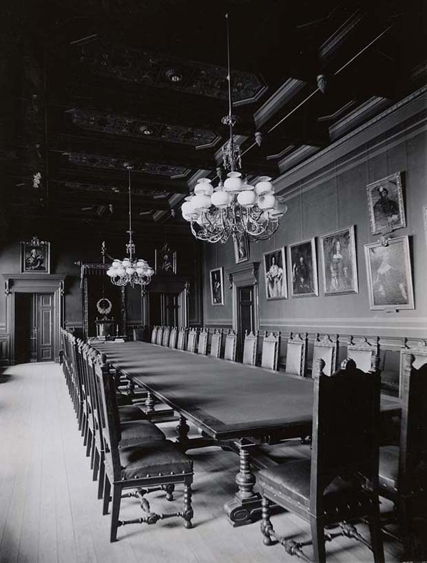 Old photo of the boards old meeting room. A long table and chairs in the middle, two chandeliers hanging from the ceiling, portraits of regents on the walls